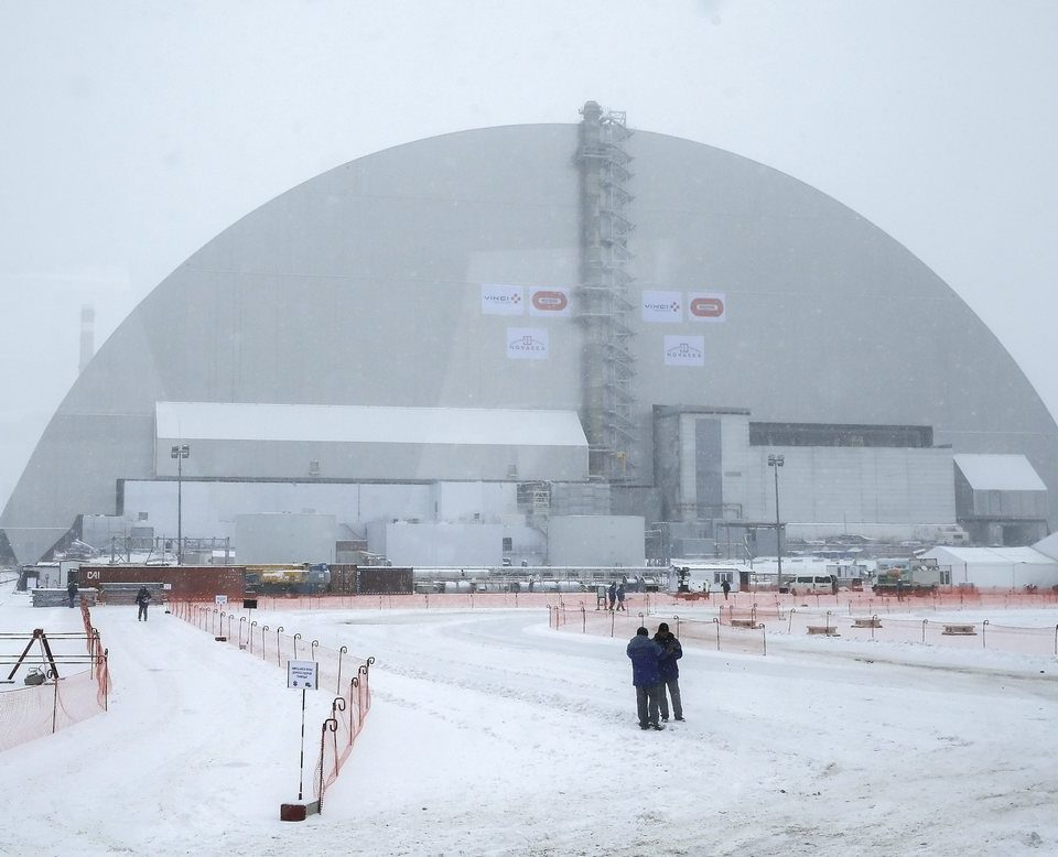 epa05651755 Picture shot through a bus window shows a general view of the new protective shelter which placed over the remains of the nuclear reactor Unit 4, at Chernobyl nuclear power plant, in Chernobyl, Ukraine, 29 November 2016. The explosion of Unit 4 of the Chernobyl nuclear power plant in the early hours of 26 April 1986 is still regarded the biggest accident in the history of nuclear power generation. Under extremely hazardous conditions a steel and concrete structure was built hastily immediately after the accident. The new concrete and steel built over the still-radioactive remains of a reactor which was melted down as a result of the accident and has 105 meters tall, 150 meters length with a width of 257 meters and a 100 years life expectancy of the confinement.  EPA/SERGEY DOLZHENKO